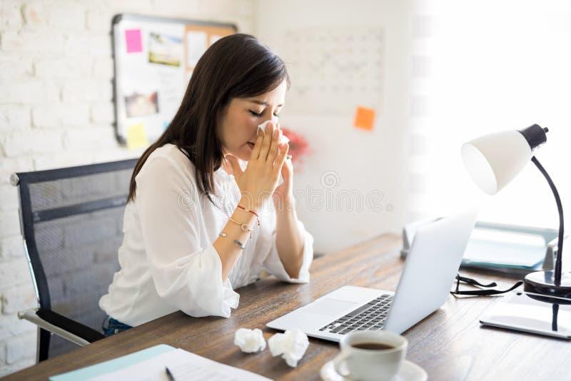 Mujer de negocios joven enferma en el trabajo foto de archivo