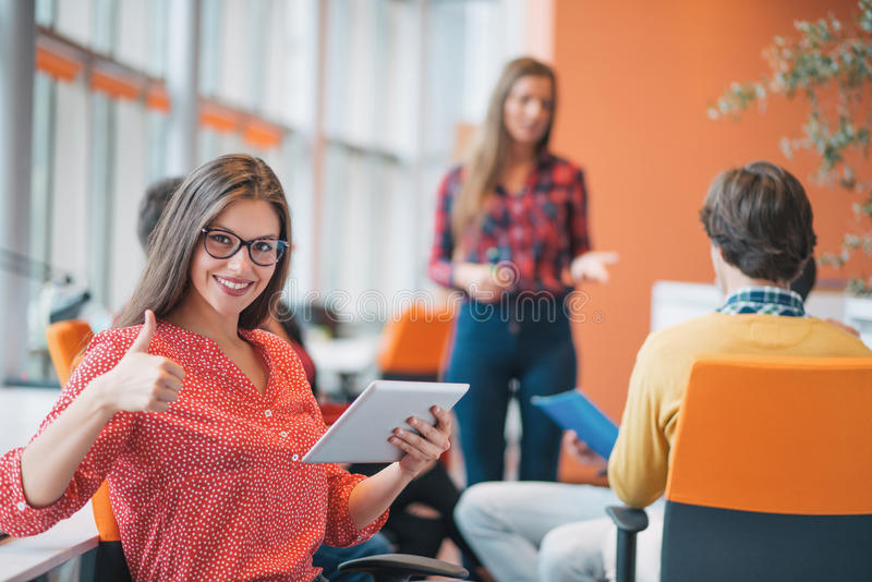 Mujer de negocios joven feliz con su personal, grupo de la gente en fondo en la oficina brillante moderna dentro imagenes de archivo