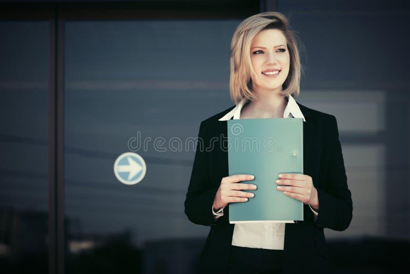 Mujer de negocios joven feliz con una carpeta contra el edificio de oficinas fotografía de archivo