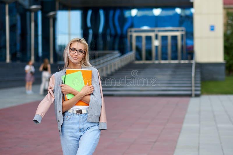Mujer de negocios joven feliz con una carpeta en el edificio de oficinas fotos de archivo libres de regalías