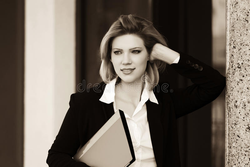 Mujer de negocios joven feliz con una carpeta que se coloca en el edificio de oficinas fotografía de archivo libre de regalías