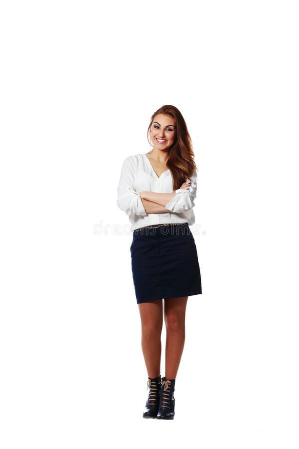Mujer de negocios joven feliz que se coloca con los brazos doblados imagen de archivo