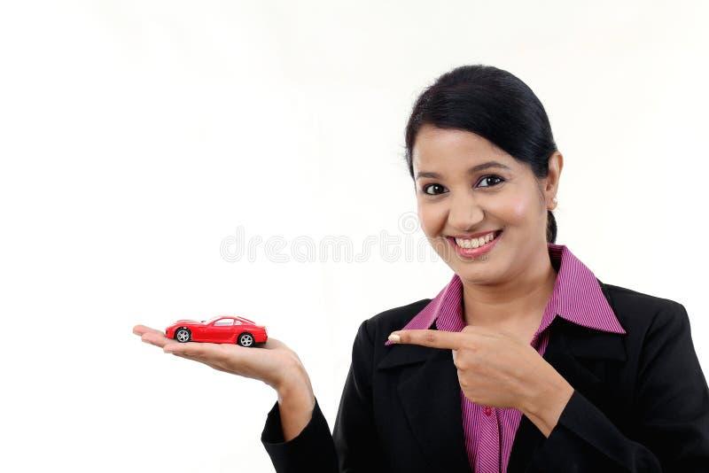 Mujer de negocios joven feliz que sostiene el coche del juguete fotografía de archivo