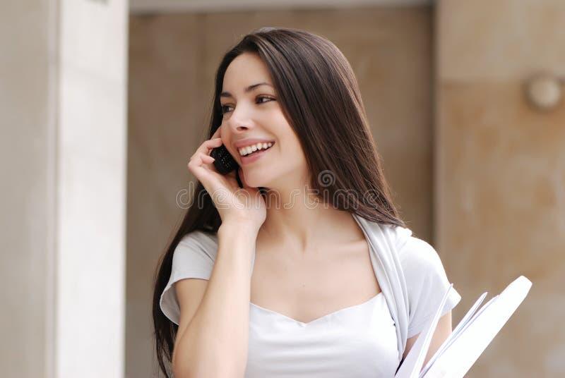 Mujer de negocios joven hermosa con el movil imagen de archivo