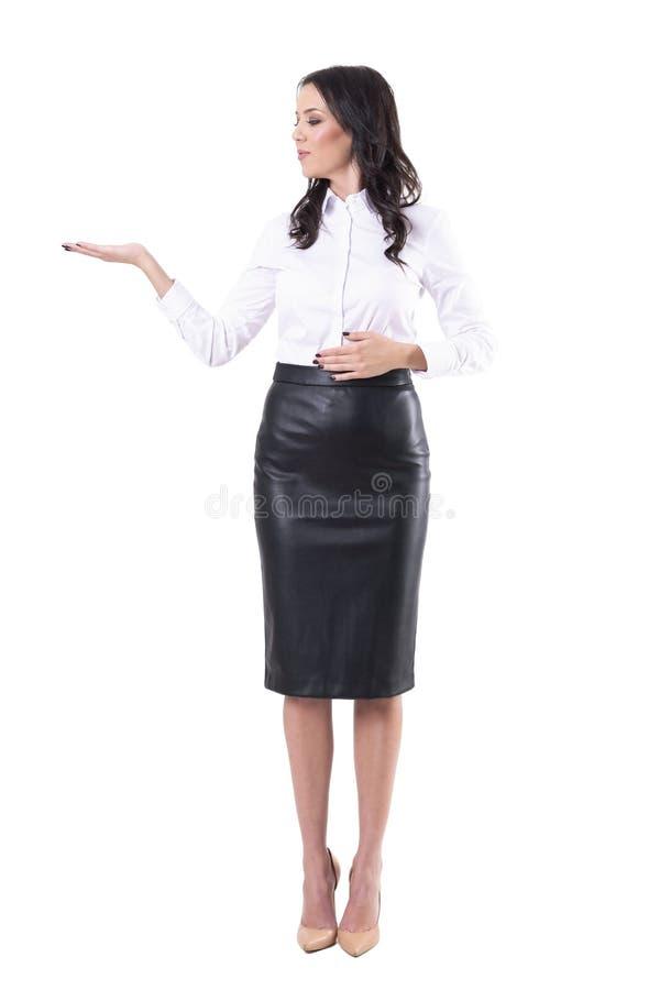 Mujer de negocios joven hermosa en el desgaste formal que vende y que muestra el espacio de la copia con la mano abierta fotos de archivo