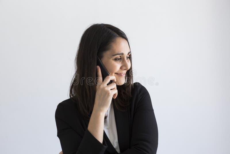 Mujer de negocios joven hermosa que habla en su teléfono móvil y sonrisa Fondo blanco Concepto del asunto lifestyles foto de archivo