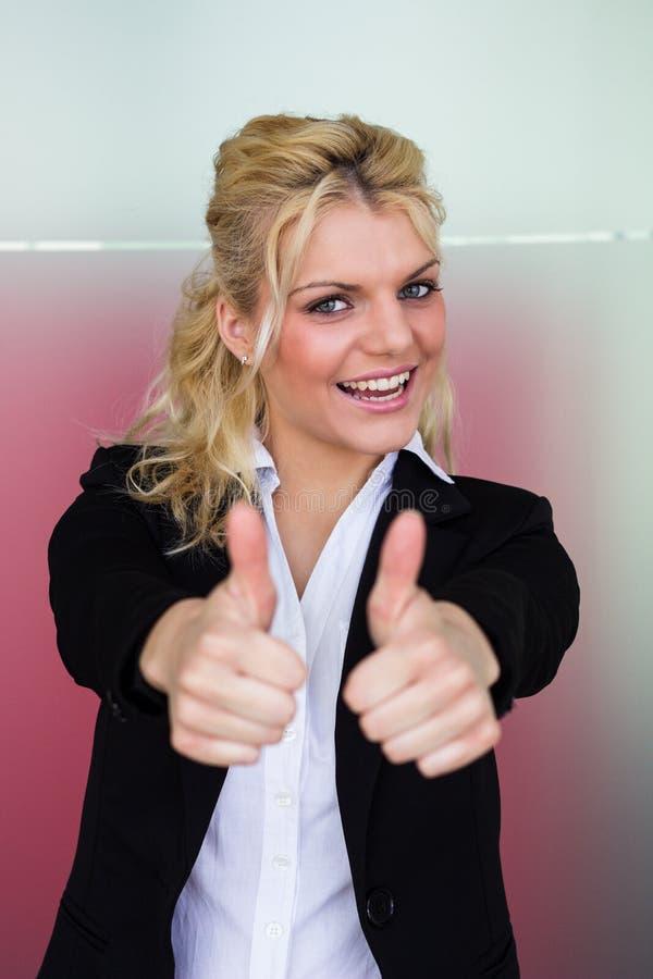 Mujer de negocios joven hermosa que muestra los pulgares para arriba fotos de archivo libres de regalías