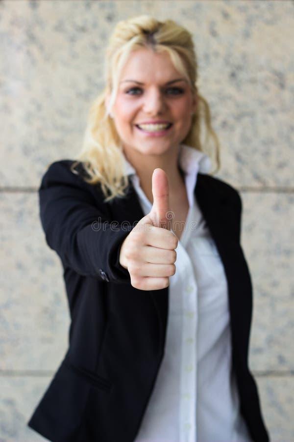 Mujer de negocios joven hermosa que muestra los pulgares para arriba imagen de archivo libre de regalías