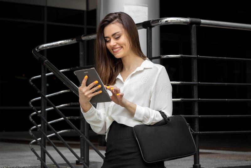 Mujer de negocios joven hermosa que sonríe y que mira la tableta imagen de archivo