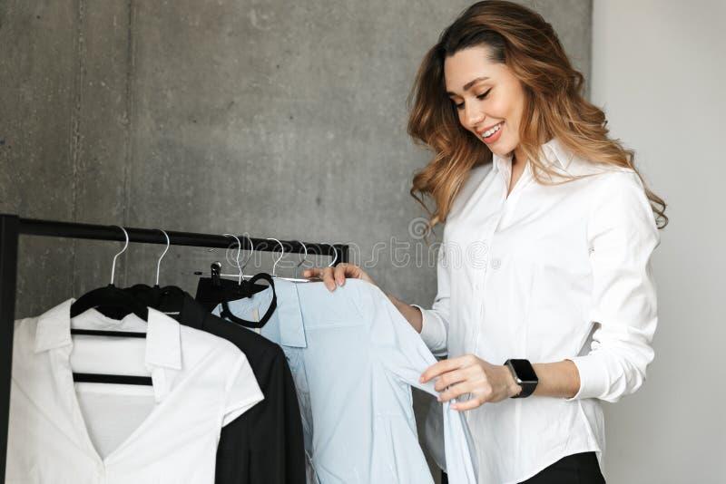 Mujer de negocios joven hermosa vestida en la camisa formal de la ropa dentro que se coloca cerca de la suspensión fotos de archivo