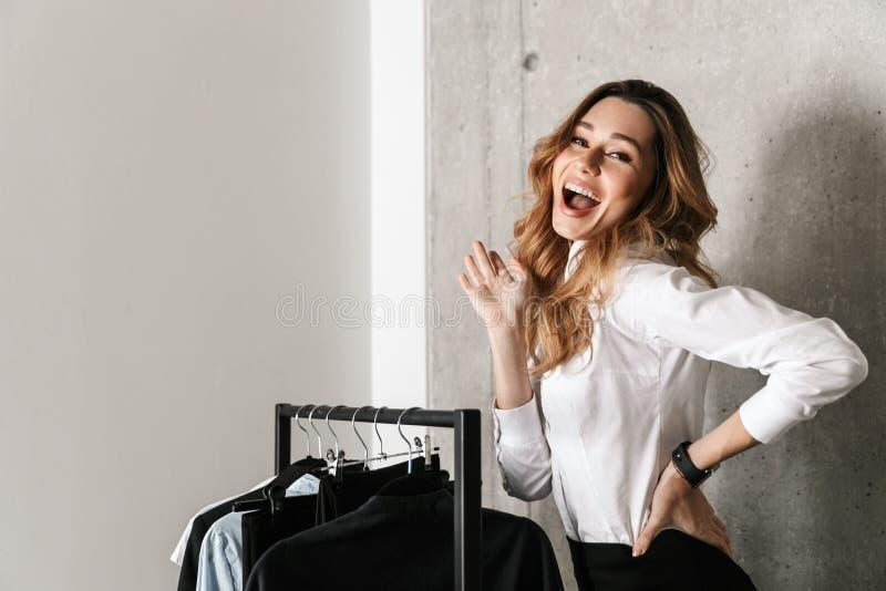 Mujer de negocios joven hermosa vestida en la camisa formal de la ropa dentro que se coloca cerca de la suspensión foto de archivo