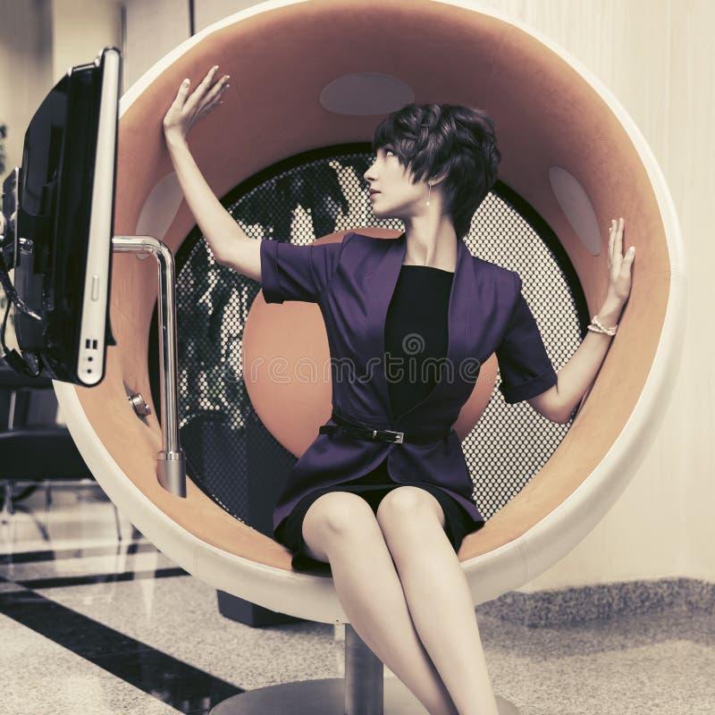 Mujer de negocios joven de moda que se sienta en silla del ordenador en oficina imágenes de archivo libres de regalías