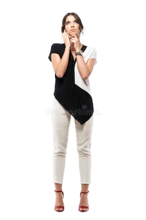 Mujer de negocios joven pensativa en el teléfono celular que habla y que mira para arriba imagen de archivo