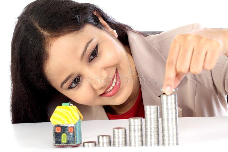 Mujer de negocios joven que arregla la pila de monedas imagenes de archivo