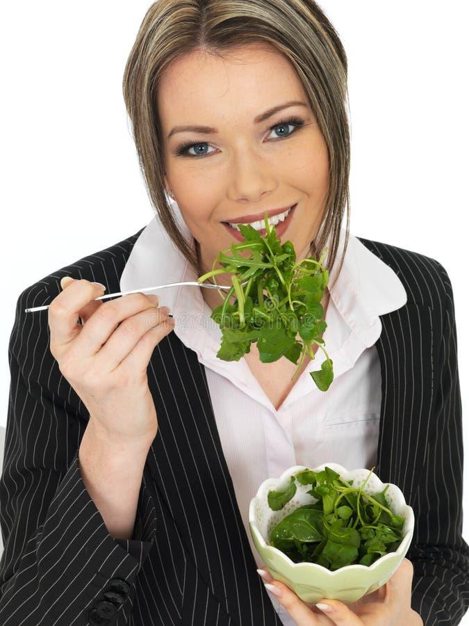 Mujer de negocios joven que come una ensalada verde fresca de la hoja imagen de archivo libre de regalías