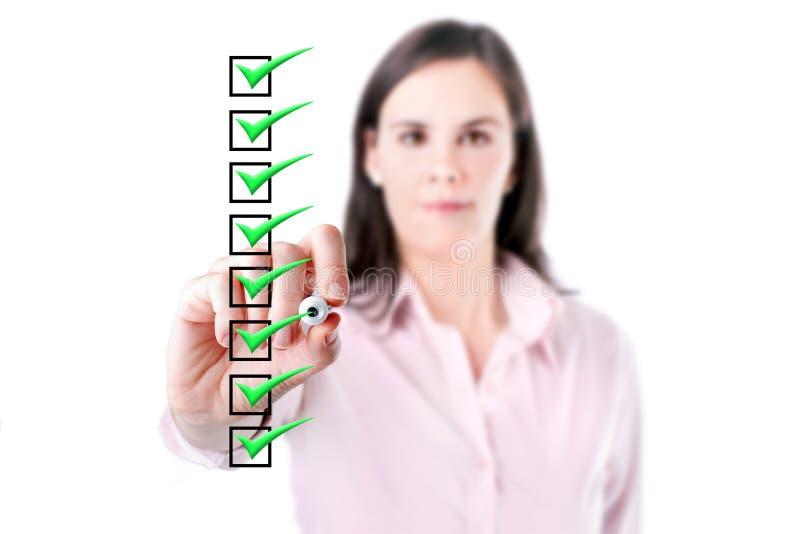 Mujer de negocios joven que comprueba las cajas de la lista de control, baclground blanco. imagen de archivo