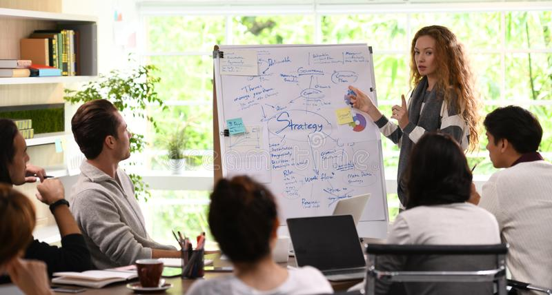 Mujer de negocios joven que da la presentación en los planes futuros imagen de archivo