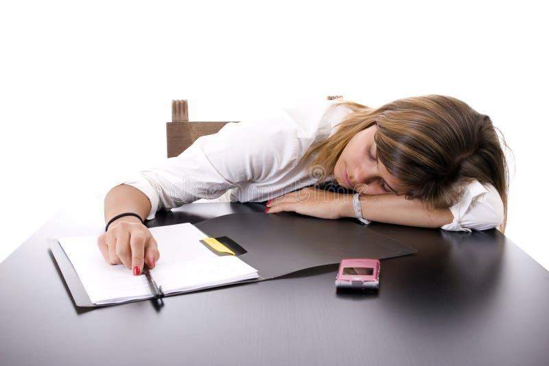 Mujer de negocios joven que duerme en el escritorio foto de archivo libre de regalías