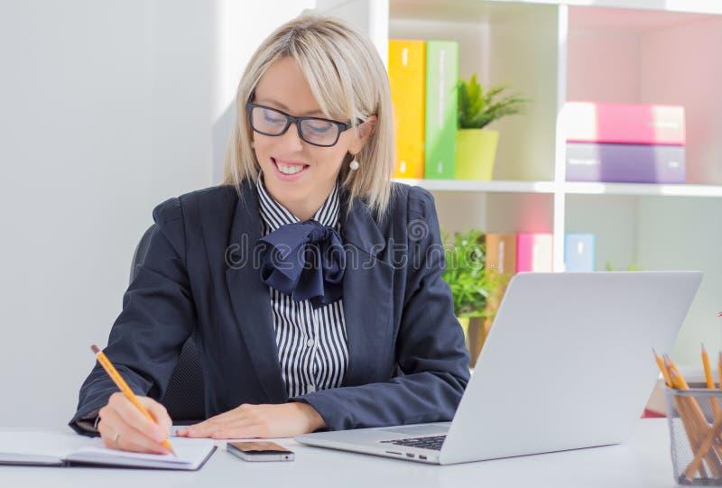 Mujer de negocios joven que escribe para hacer la lista mientras que se sienta en su escritorio imagen de archivo