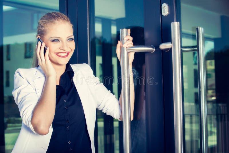 Mujer de negocios joven que habla un teléfono móvil en la calle contra el edificio fotografía de archivo