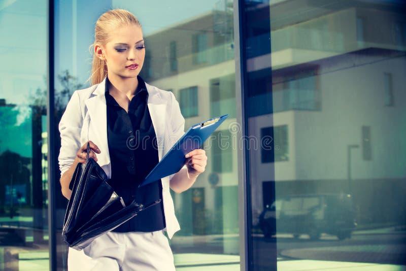 Mujer de negocios joven que habla un teléfono móvil en la calle contra el edificio foto de archivo