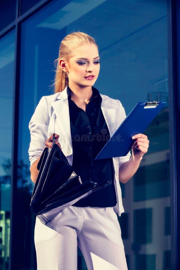 Mujer de negocios joven que habla un teléfono móvil en la calle contra el edificio imagenes de archivo