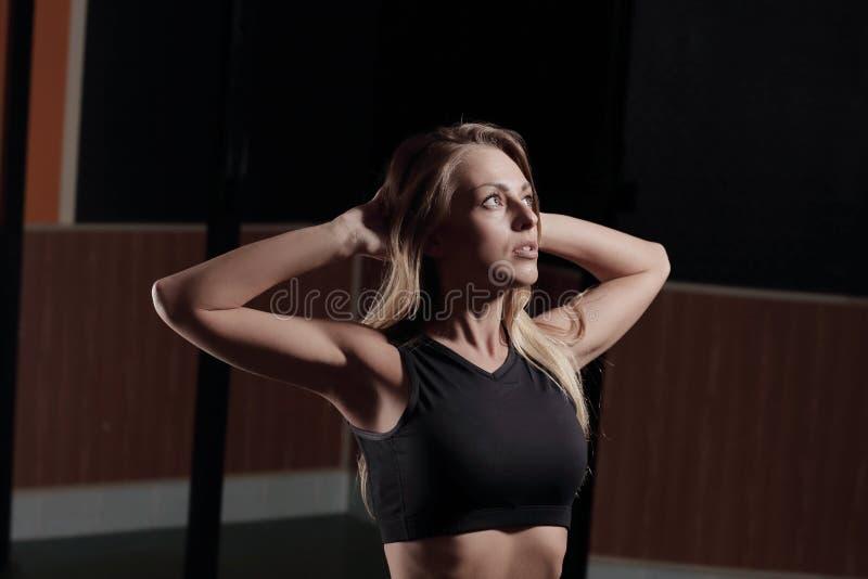 Mujer de negocios joven que hace ejercicios en el centro de aptitud imagen de archivo