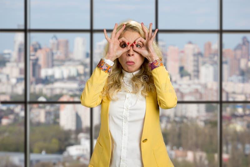 Mujer de negocios joven que hace las manos de los prismáticos fotos de archivo libres de regalías