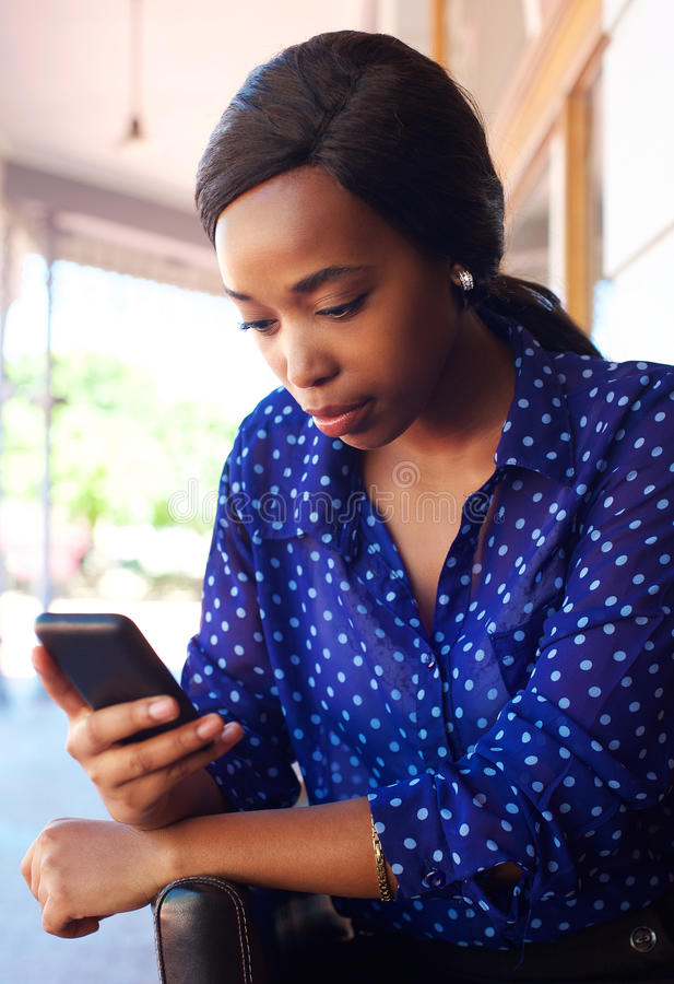 Mujer de negocios joven que mira el teléfono móvil foto de archivo libre de regalías