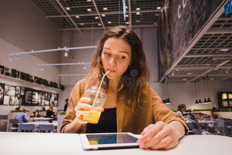 Mujer de negocios joven que mira la tableta y que bebe el jugo de la paja en restaurante foto de archivo