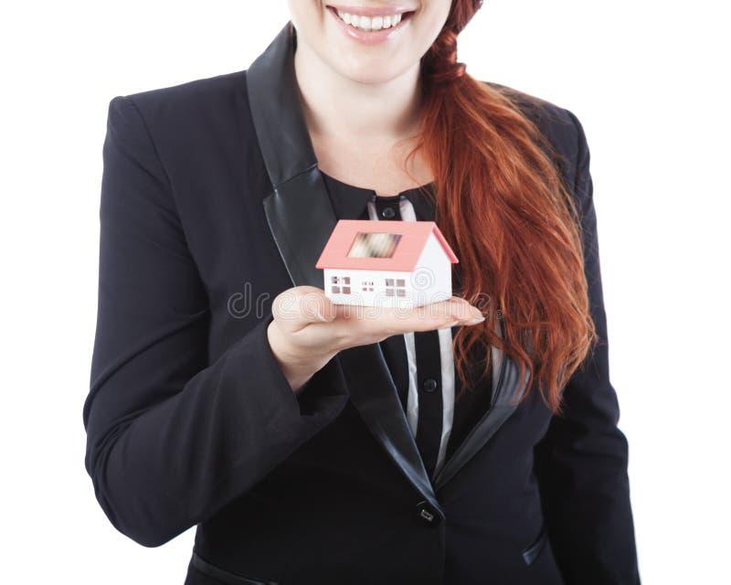 Mujer de negocios joven que muestra la mini casa en su mano imagen de archivo