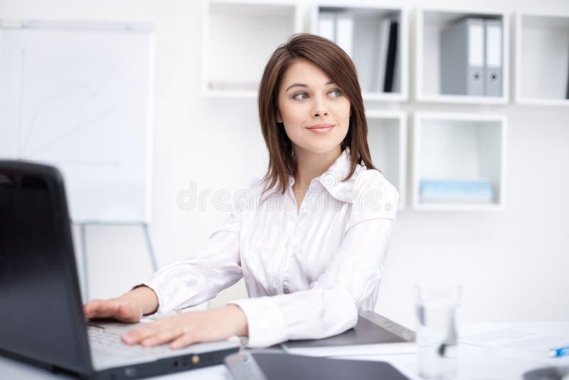 Mujer de negocios joven que se sienta en el escritorio en la oficina fotografía de archivo