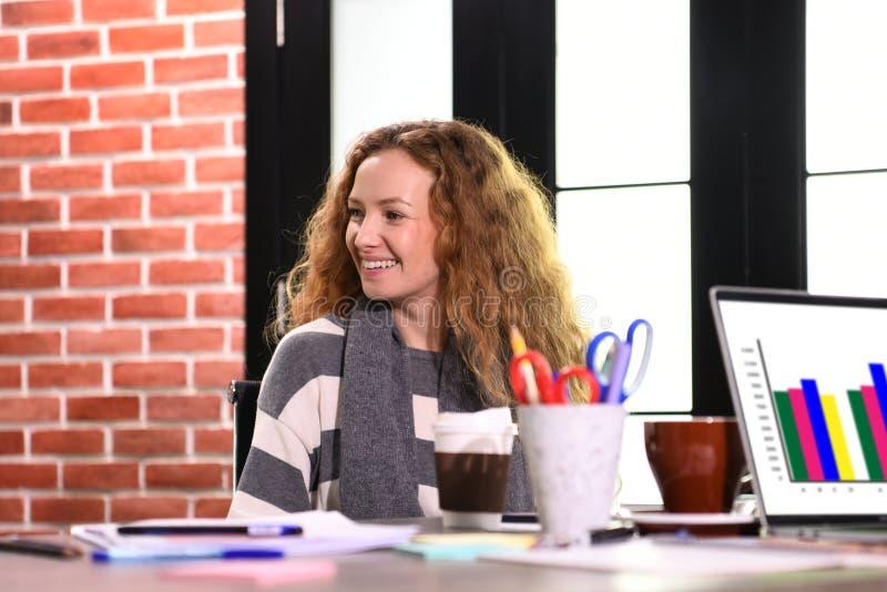 Mujer de negocios joven que se sienta en el escritorio en oficina imagen de archivo