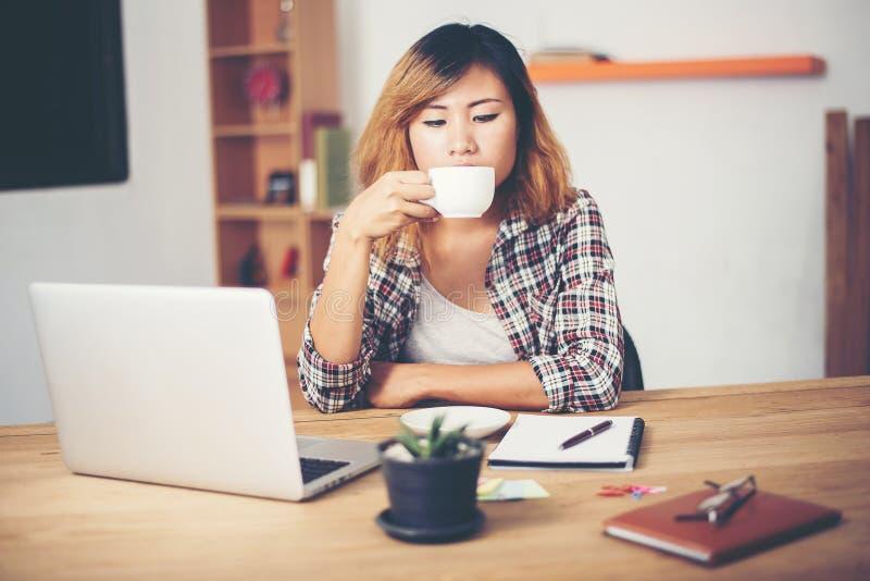 Mujer de negocios joven que se sienta en escritorio de oficina con la taza del café r fotos de archivo