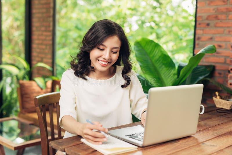 Mujer de negocios joven que se sienta en la tabla en café y que escribe adentro no foto de archivo