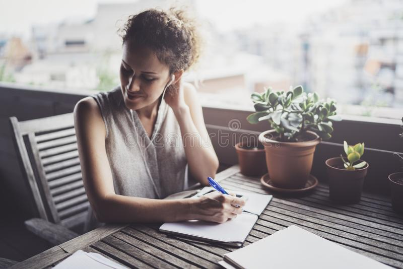 Mujer de negocios joven que se sienta en la tabla en terraza del caffee y que toma notas en cuaderno En la tabla es el smartphone imagen de archivo libre de regalías