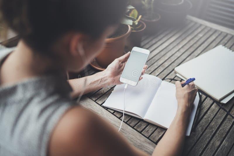 Mujer de negocios joven que se sienta en la tabla en terraza del caffee y que toma notas en cuaderno En la tabla es el smartphone fotografía de archivo