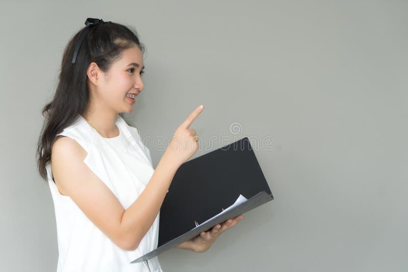 Mujer de negocios joven que sonríe sosteniendo el fichero de documento que señala la mano imagenes de archivo