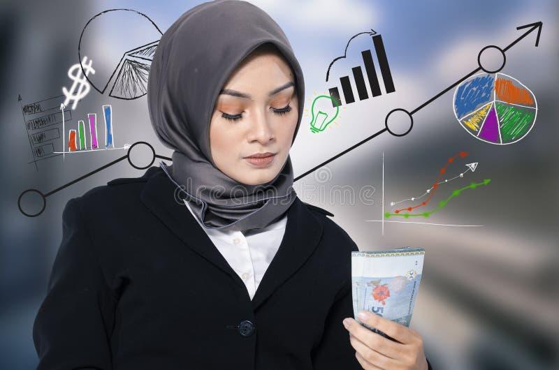 Mujer de negocios joven que sostiene el billete de banco sobre fondo abstracto con símbolos financieros fotografía de archivo libre de regalías