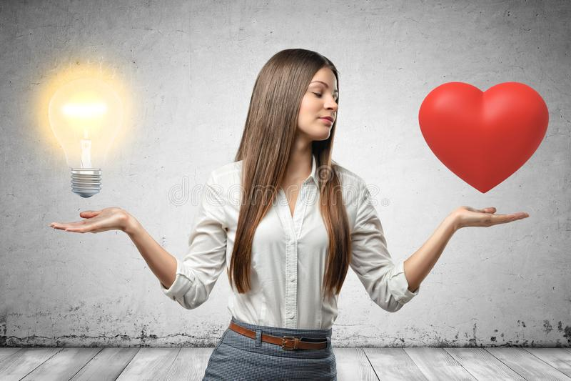Mujer de negocios joven que sostiene el bulbo del corazón rojo y de la luz ámbar en sus manos en fondo gris de la pared imagen de archivo libre de regalías