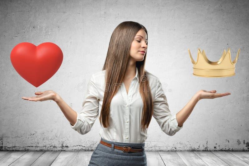 Mujer de negocios joven que sostiene el corazón rojo y la corona de oro en sus manos en fondo gris de la pared Fondo fotos de archivo libres de regalías