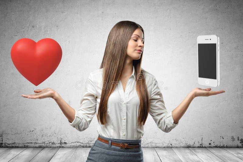 Mujer de negocios joven que sostiene el coraz?n y el smartphone rojos en sus manos en fondo gris de la pared foto de archivo