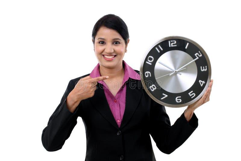 Mujer de negocios joven que sostiene el reloj en manos foto de archivo libre de regalías