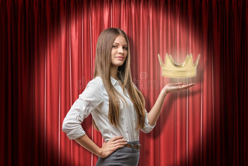 Mujer de negocios joven que sostiene la corona de oro en fondo rojo de las cortinas de la etapa ilustración del vector