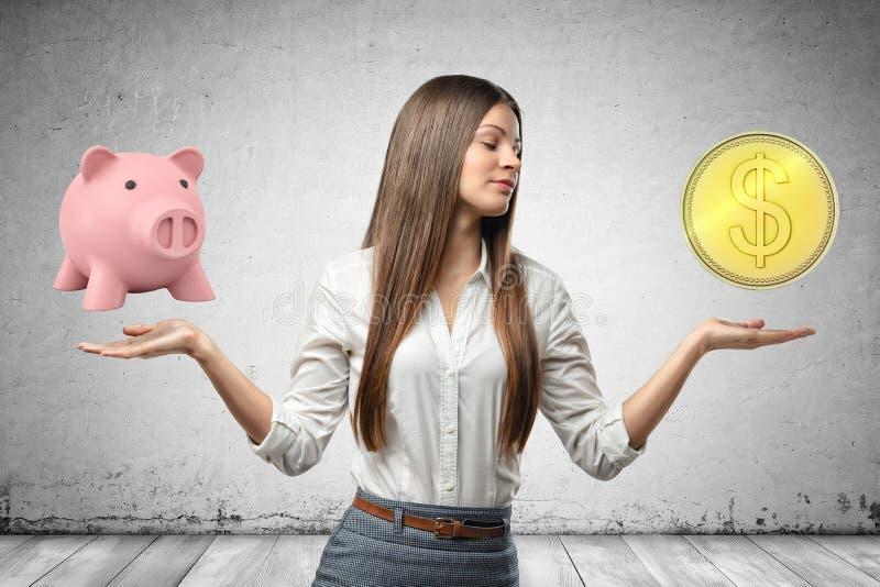 Mujer de negocios joven que sostiene la hucha rosada y la moneda de oro del dólar en sus manos en fondo gris de la pared fotografía de archivo libre de regalías