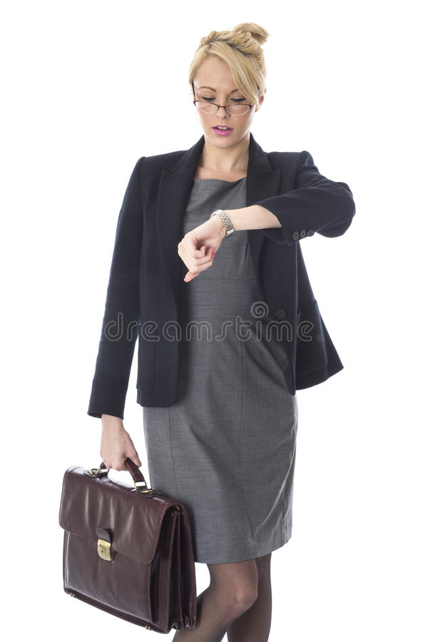 Mujer de negocios joven que sostiene una cartera que mira el reloj foto de archivo