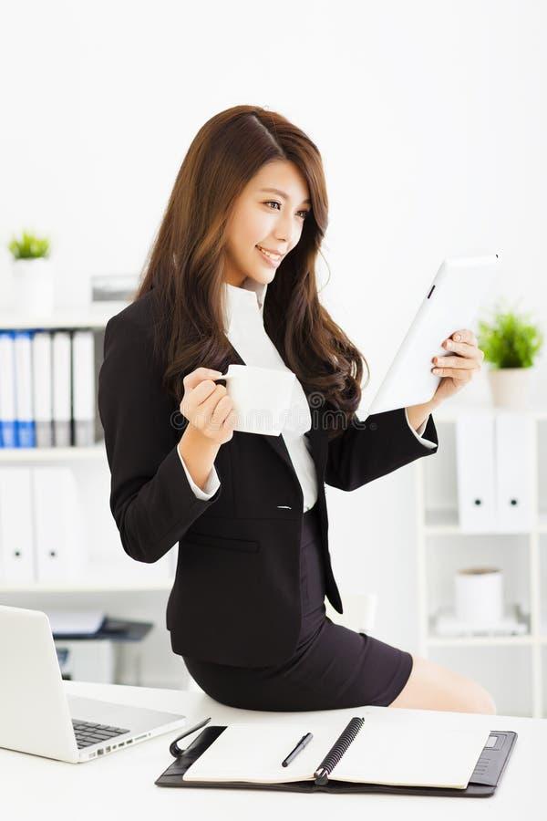 mujer de negocios joven que trabaja con la tableta en oficina imágenes de archivo libres de regalías