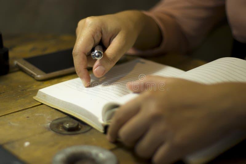 Mujer de negocios joven que trabaja con una pluma en la oficina, ella que permanece en horas extras imagen de archivo libre de regalías