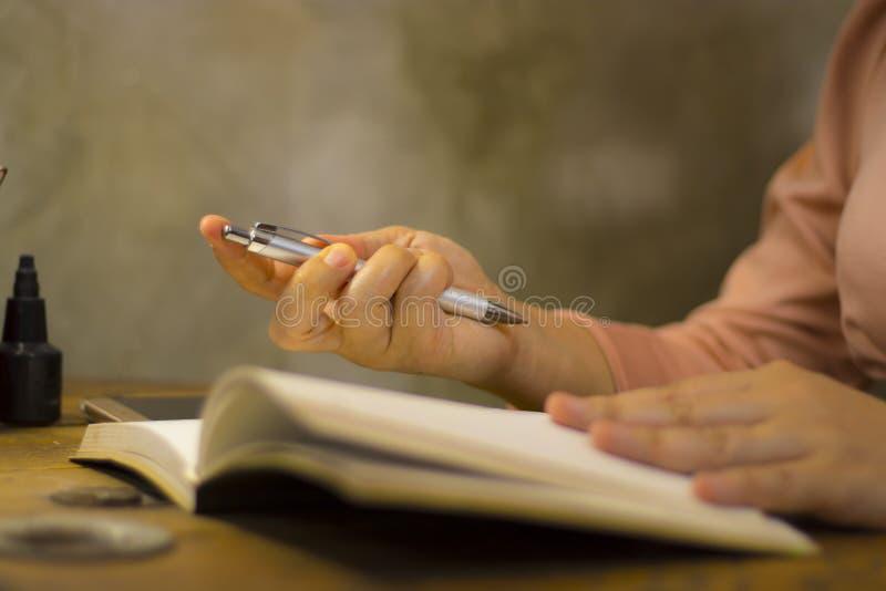 Mujer de negocios joven que trabaja con una pluma en la oficina, ella que permanece en horas extras imágenes de archivo libres de regalías