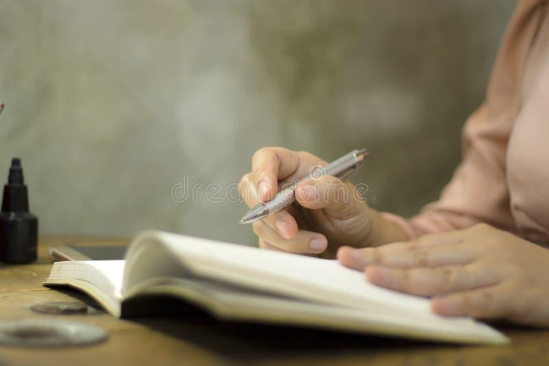 Mujer de negocios joven que trabaja con una pluma en la oficina, ella que permanece en horas extras fotografía de archivo libre de regalías